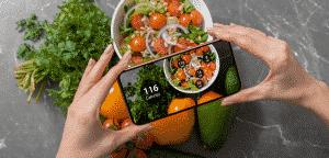 Fille prenant une photo de nourriture végétarienne sur table avec son smartphone