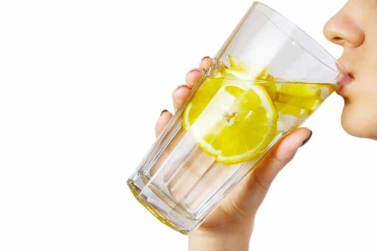 individu buvant un verre d'eau avec citron