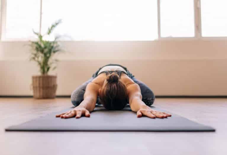 femme sur grand tapis de yoga